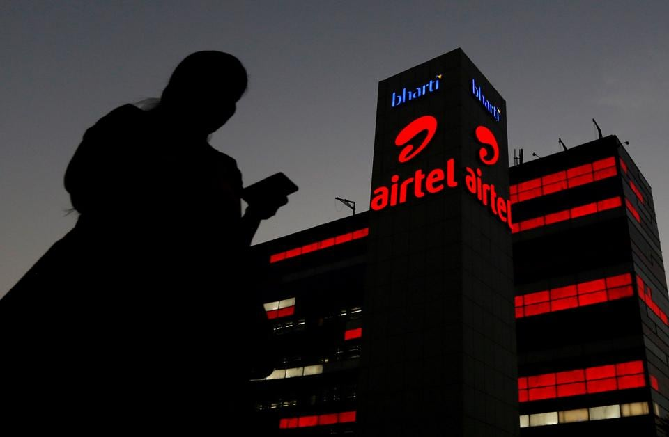 A girl checks her mobile phone as she walks past the Bharti Airtel office building in Gurugram, previously known as Gurgaon, on the outskirts of New Delhi, India April 21, 2016.