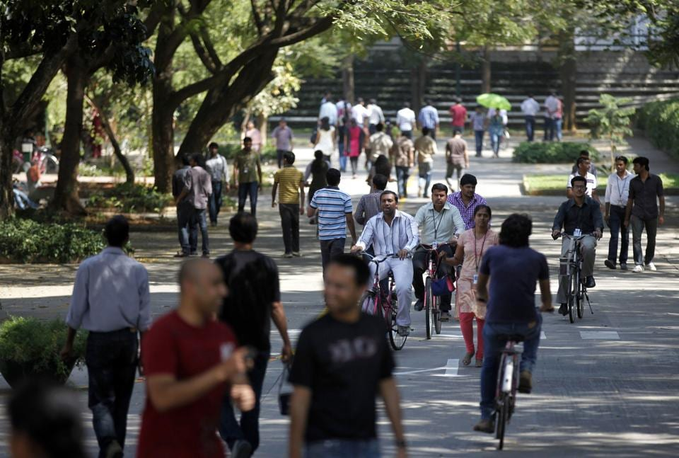 Infosys Technologies employees move through the headquarters during a break in Bangalore, India. The shares of top Indian IT companies are falling in response to news of proposed U.S. legislation that would require salaries for H-1B visa holders to be doubled to make it harder for companies to replace American workers with those from countries like India.