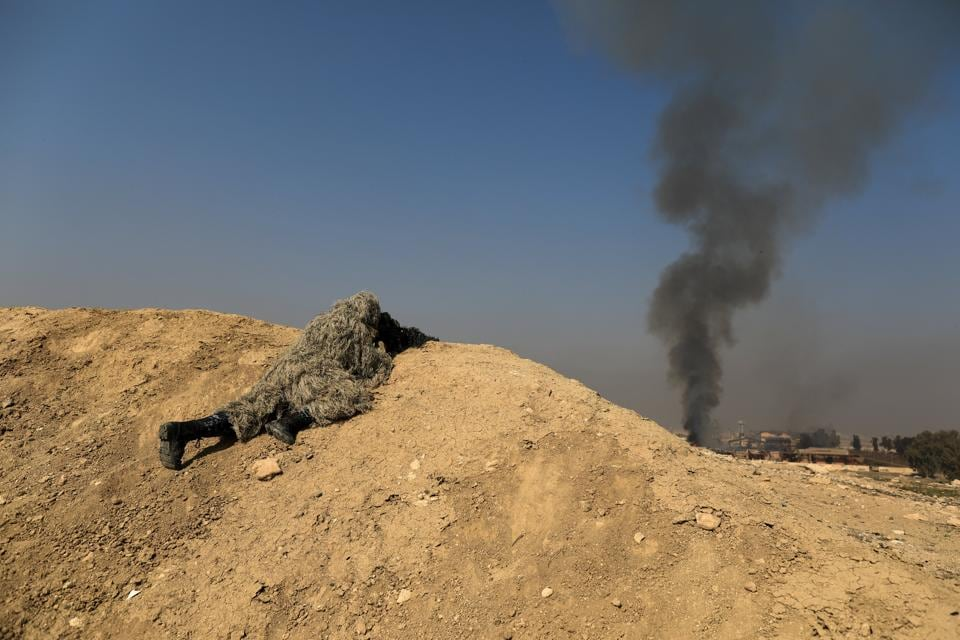 Smoke rises from a factory as an Iraqi security forces sniper aims his weapon towards Mosul airport during a battle with Islamic State militants in Mosul on Thursday.