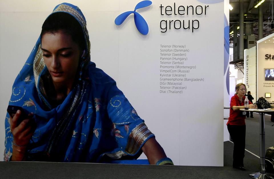 A visitor rests under a Telenor Group sign at the GSMA Mobile World Conference in Barcelona, Spain.