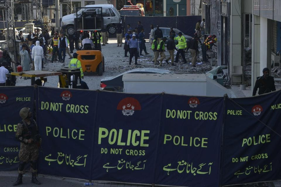 Pakistani security officials examine the site of the attack in Lahore on Wednesday.