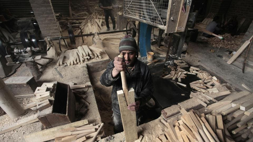 A worker fits a handle into a spliced bat. Each craftsman at the site refines up to 100 bats a day, chiselling and planing the wood into the shape of a bat before the handle is attached.  (Waseem Andrabi  / HT Photo)