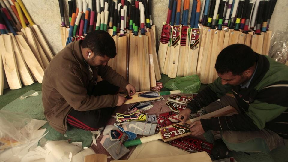 Pasting stickers on the now nearly finished cricket bats. (Waseem Andrabi  / HT Photo)