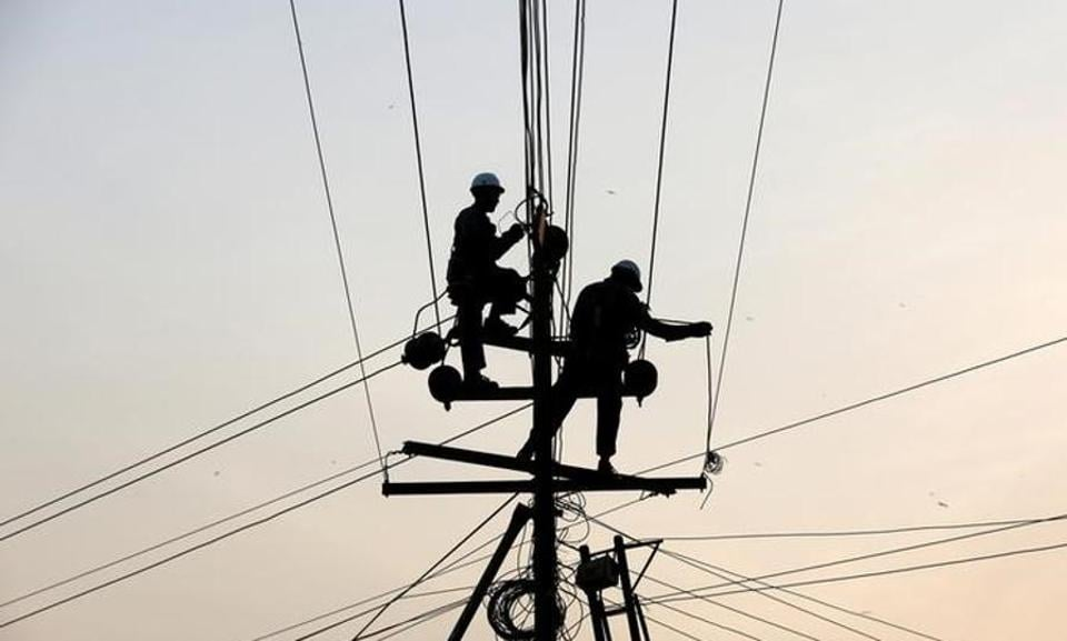Technicians  work on power transmission lines.