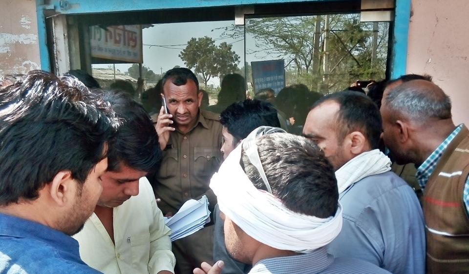 Locals gather near the property dealer's office at Fazilpur crossing after the firing incident