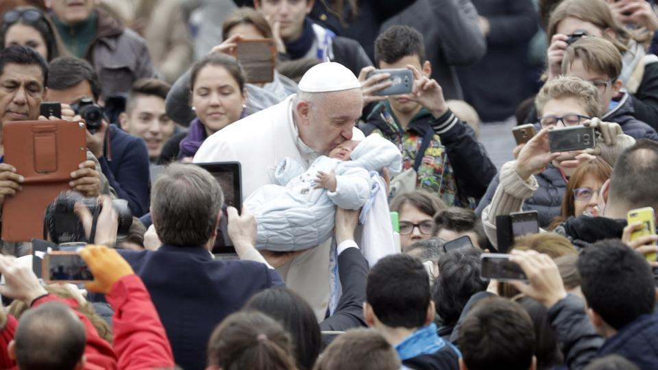 Pope Francis kisses a baby as he is driven through the crowd during his weekly general audience at St. Peter's Square in the Vatican on Wednesday.