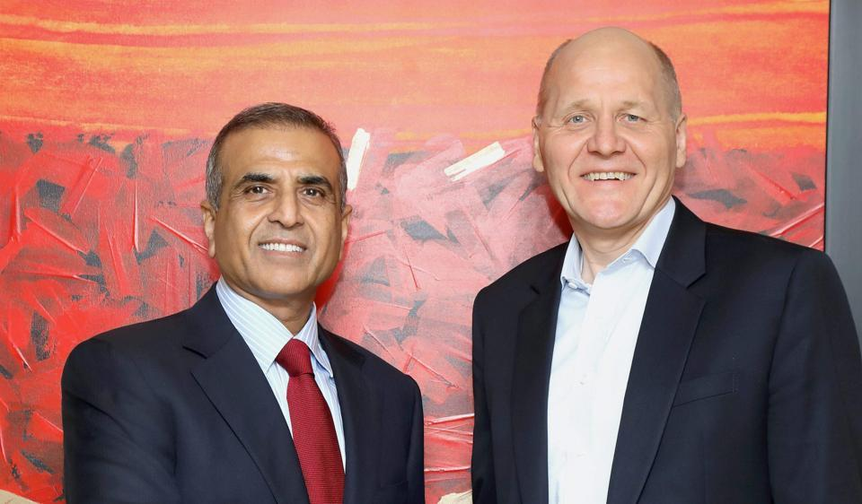 Sunil Bharti Mittal, Founder and Chairman, Bharti Enterprises shakes hands with Sigve Brekke, Chief Executive Officer, Telenor Group after the announcement of Airtel's acquisition of Telenor (India) in New Delhi.