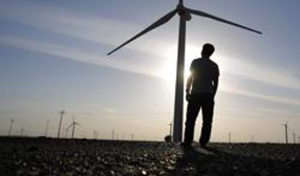 A worker stands in a wind farm in Guazhou, in China.
