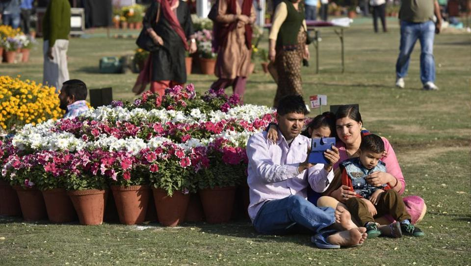 A family poses for a selfie on the first day of Noida flower show.