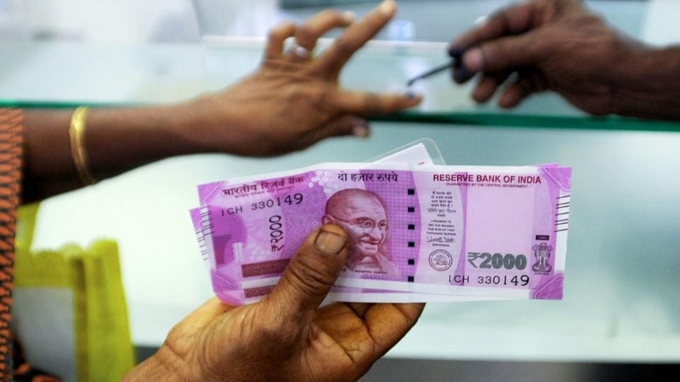 A woman holds Rs 2000 notes as she exchanges demonetised notes at a bank in Chennai.