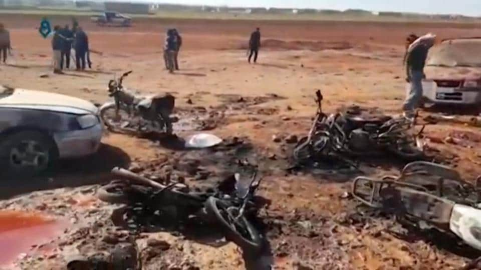 An image taken from a video posted on social media on February 24 shows people inspecting the site of a car bomb explosion in Sousian village near Al-Bab in Syria.
