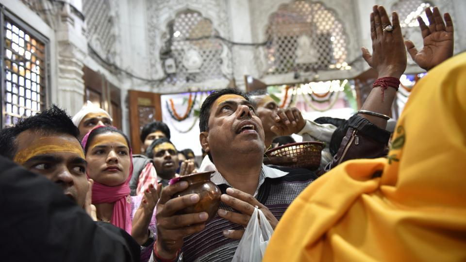 A devotee looks up during morning prayers at a temple. (Saumya Khandelwal/HT PHOTO)