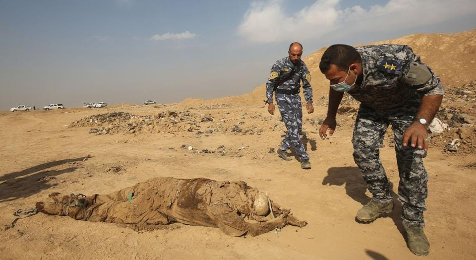 This file photo taken on November 7, 2016 shows members of the Iraqi forces checking a body they pulled from a mass grave they discovered in the Hamam al-Alil area after they recaptured the area from Islamic State (IS) group jihadists.