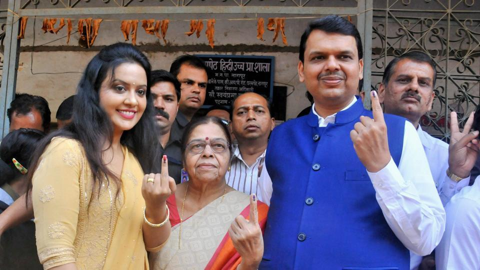 Maharashtra chief minister Devendra Fadnavis with mother (C) and wife Amruta (R) after casting his vote on the municipal elections in Nagpur of Maharashtra on Tuesday.