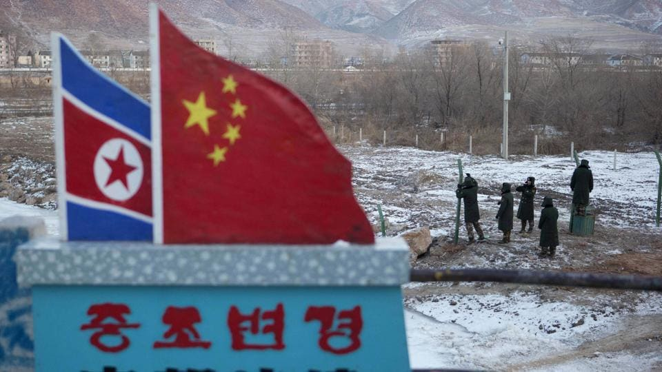 File photo from  2012 shows Chinese paramilitary policemen building a fence near a concrete marker depicting the North Korean and Chinese national flags with the words