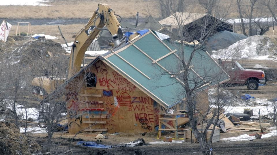 A backhoe rips through a wood structure to begin the cleaning up process at the Oceti Sakowin camp as law enforcement swept through the camp arresting the final Dakota Access oil pipeline protesters in Morton County. (Mike McCleary/The Bismarck Tribune via AP)