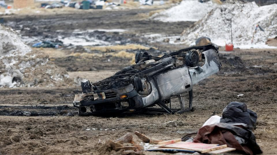 A burned car rests on its roof in the main opposition camp. The state sent a bus to the site on Thursday to transport anyone to Bismarck, where officials were doling out basic necessities, along with hotel and bus vouchers. (Terray Sylvester/REUTERS)