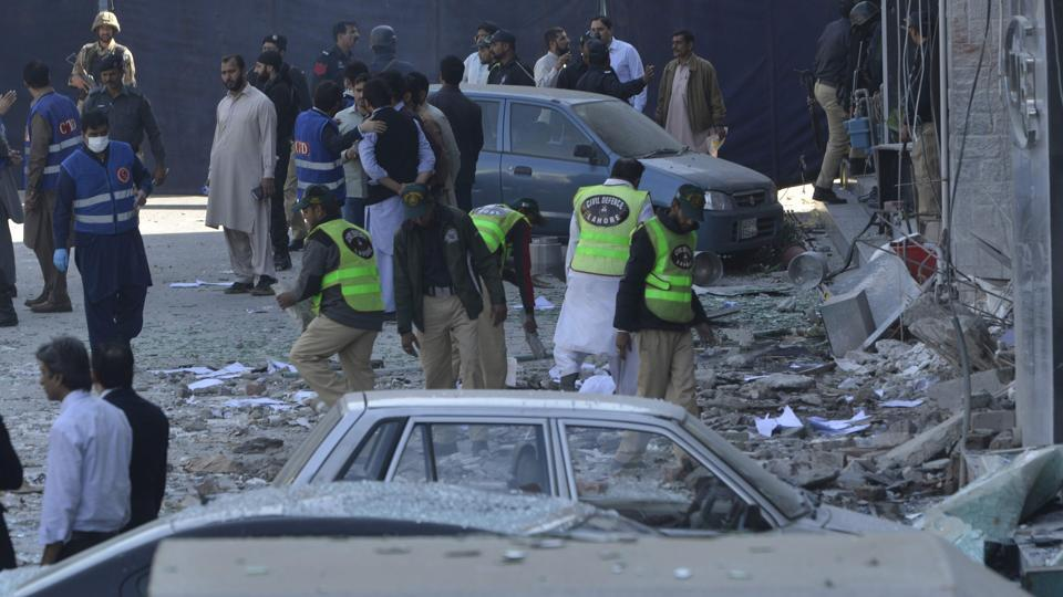Pakistani security officials examine the site after a bomb attack in Lahore on February 23, 2017.