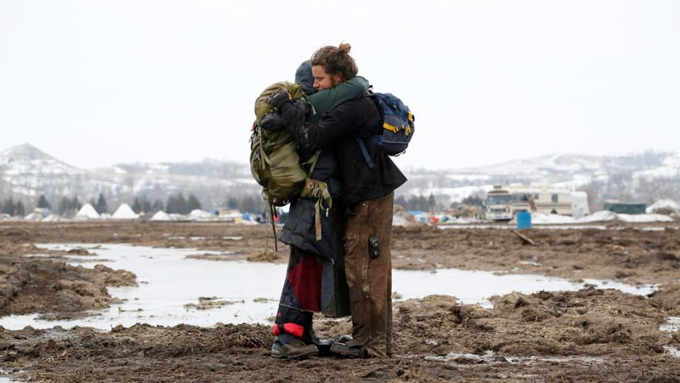 Susanna Travis (left), from Grass Valley, California, embraces Timothy Powers, also from California, before evacuating the opposition camp.  (Terray Sylvester/REUTERS)