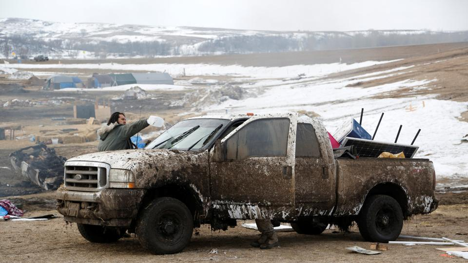 A protester washes mud from his truck before evacuating. As police in full riot gear worked to arrest the stragglers Thursday, cleanup crews began razing buildings on the square-mile piece of property at the confluence of the Cannonball and Missouri rivers. (Terray Sylvester/REUTERS)