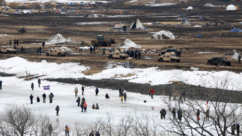 Protesters confront police from the surface of the frozen Cannon Ball River after being driven from the main opposition camp against the Dakota Access oil pipeline.  (Terray Sylvester/REUTERS)