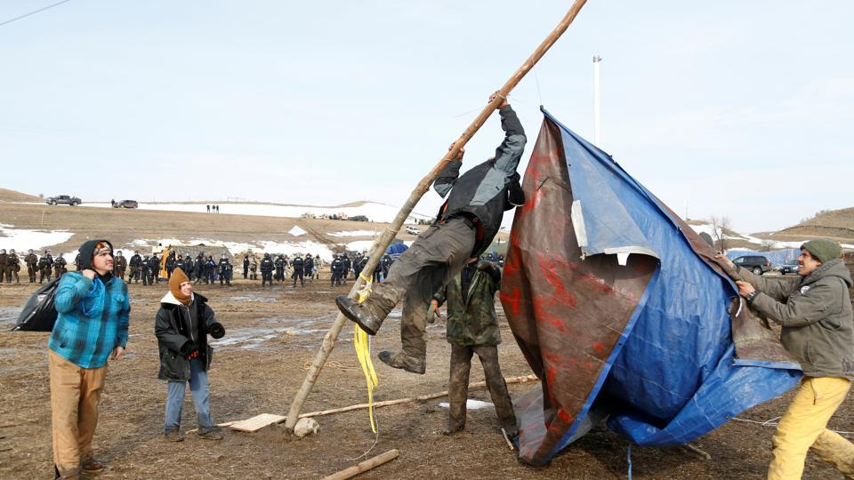 Protesters salvage a banner as law enforcement officers advance into the main opposition camp. (Terray Sylvester/REUTERS)