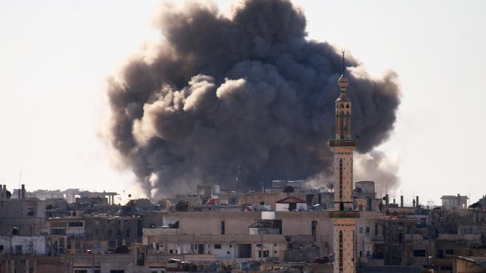 Smoke billows from the rebel-held area of Daraa in southern Syria following an air strike.