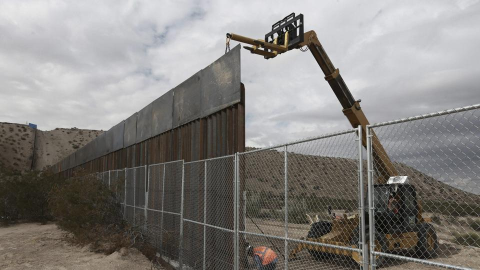 In this November 10, 2016, file photo, workers continue work raising a taller fence in the Mexico-US border area separating the towns of Anapra, Mexico and Sunland Park.