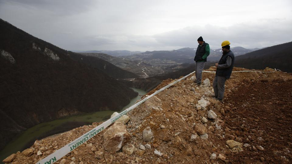 Workers survey the damage after a landslide near the Bosnian town of Kakanj, 50 km from Sarajevo. More than 150 people have been evacuated.