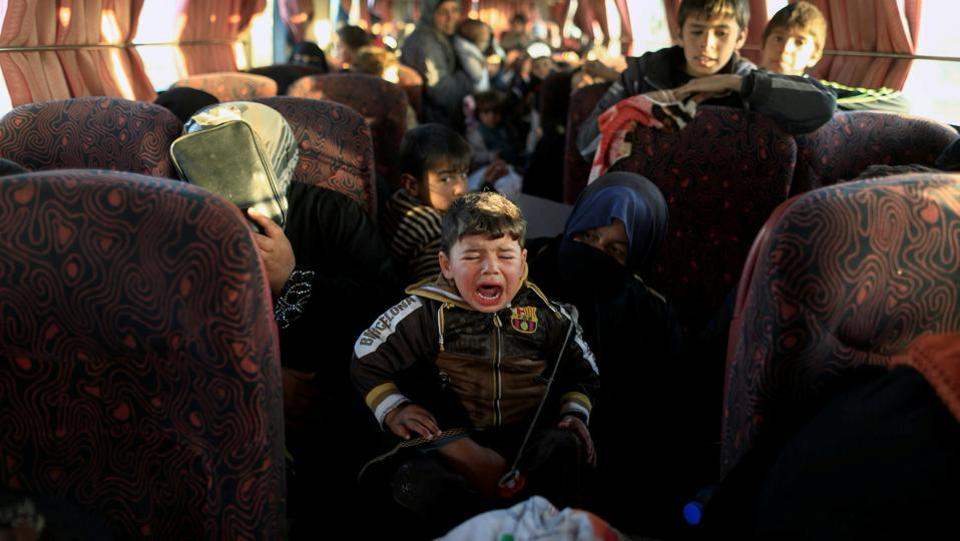 A boy, who just fled a village controlled by Islamic State fighters cries as he sits with his family inside a bus before heading to the camp at Hammam Ali south of Mosul, Iraq. (Zohra Bensemra/REUTERS)
