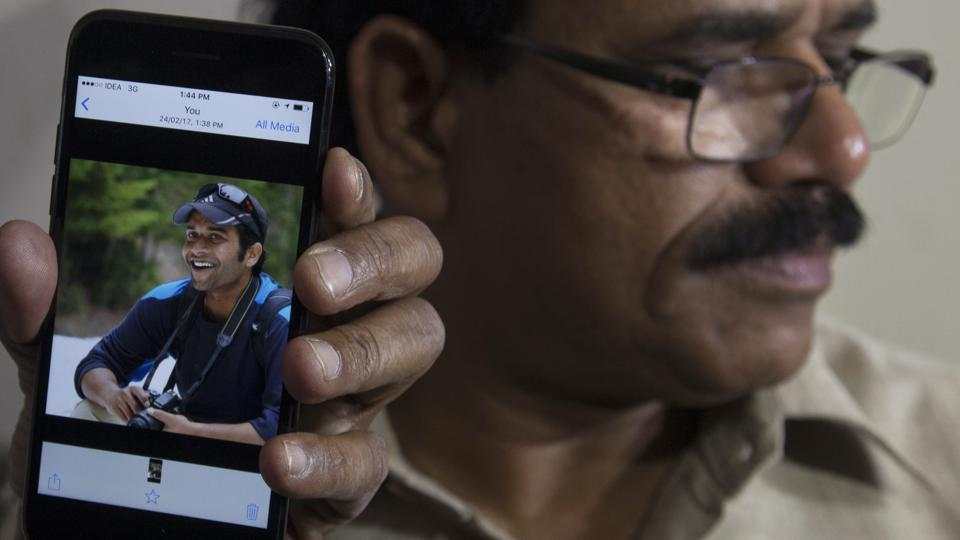 A man shows a picture of Alok Madasani, an engineer who was injured in the shooting Wednesday night in a crowded suburban Kansas City bar, on a mobile phone as Madasani's father Jaganmohan Reddy talks to the media at his residence in Hyderabad on Feb 24.
