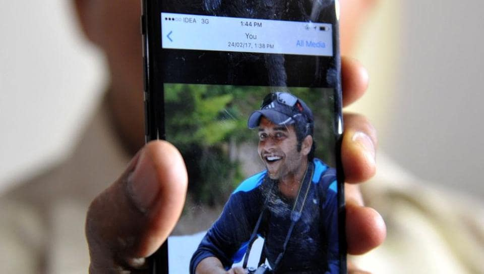 Jagan Mohan Reddy holds a smartphone with an image of his son Alok Madasani at his residence in Hyderabad on February 24, 2017, after Alok was injured in a shooting in the US state of Kansas.