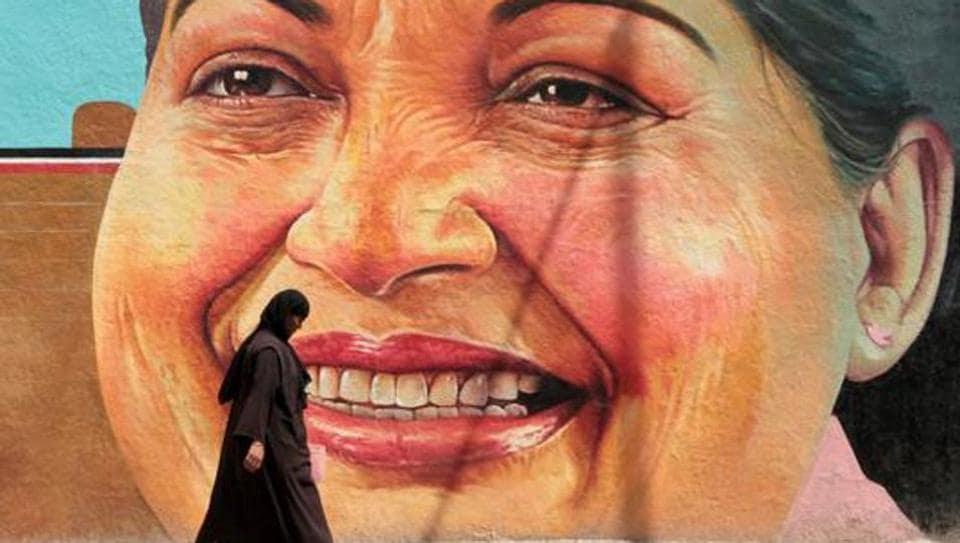 A woman walks past a portrait of J Jayalalithaa in Chennai.