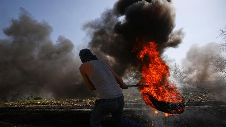 A Palestinian protester moves a burning tyre during clashes with Israeli troops following a protest against the nearby Jewish settlement of Qadomem, in the West Bank village of Kofr Qadom near Nablus. (Mohamad Torokman/REUTERS)
