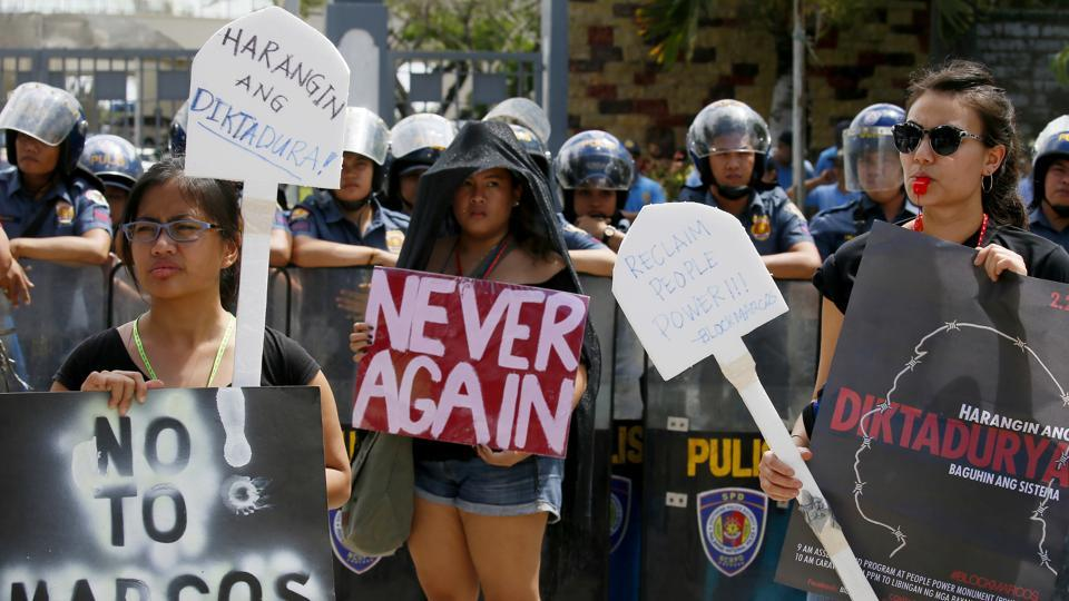 Protesters display placards during a rally at the Heroes Cemetery to protest the hero's burial accorded the late Philippine dictator Ferdinand Marcos as the nation marks the 31st anniversary of the People Power revolution that toppled the Marcoses from 20-year-rule.