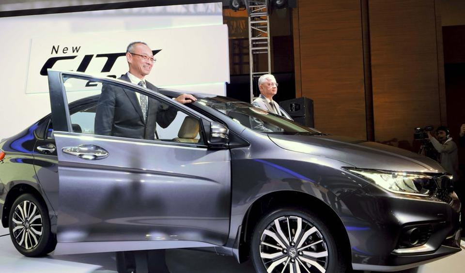 Chief executive and president of Honda Cars India Ltd, Yoichiro Ueno with SVP and director Raman Kumar Sharma (R) pose for a photograph during the launch of Honda City 2017 car in New Delhi on  February 14, 2017.