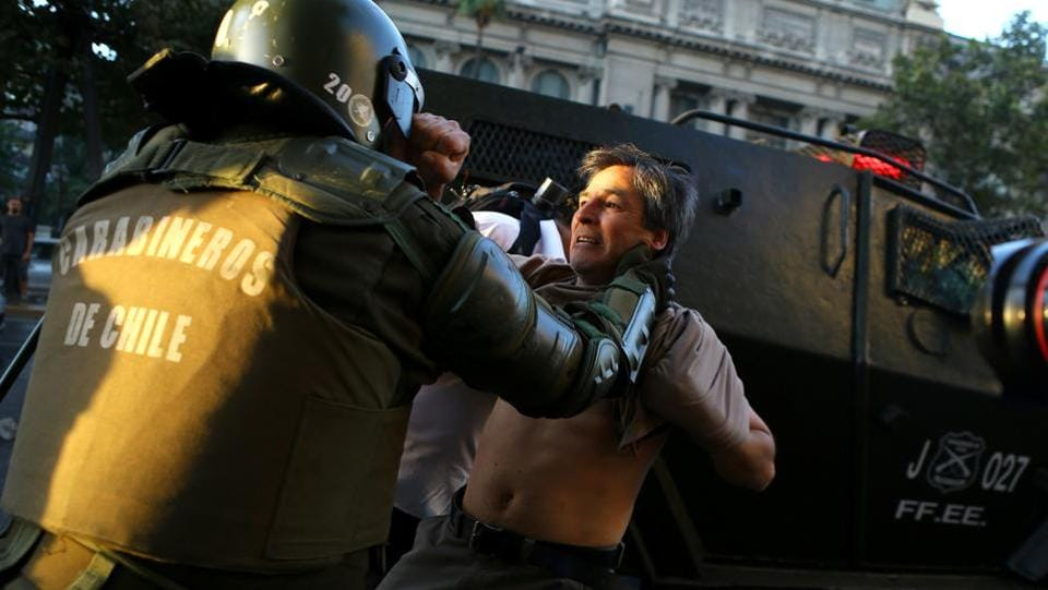 A riot policeman tries to detain a protester during a rally marking the anniversary of the death of union leader Juan Pablo Jimenez, in Santiago, Chile. (Ivan Alvarado/REUTERS)