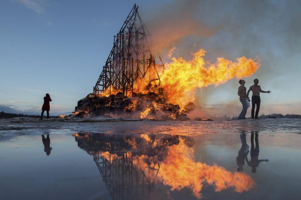 People react as a sculpture is burning at the Maslenitsa festival at the Nikola-Lenivets art park in south-west of Moscow, Russia.  (AP)