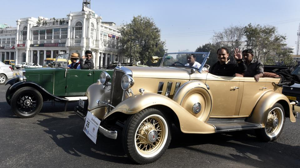 Participants waving at the onlookers from a 1933 Chevrolet Golden Eagle at the vintage car rally in New Delhi on Sunday. (Sonu Mehta/HT PHOTO)