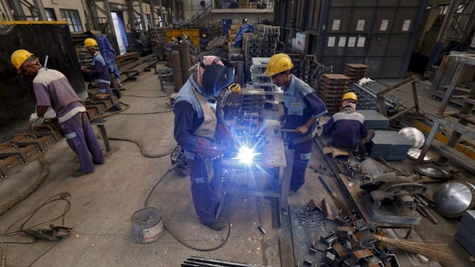 Employees make iron parts for bridges at a manufacturing unit in an industrial area on the outskirts of Kolkata.
