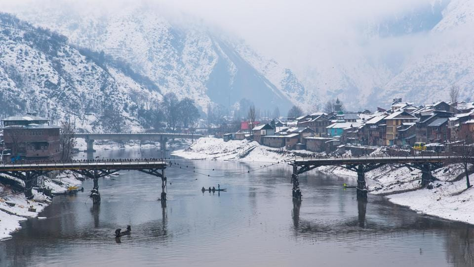A boat passes under the half collapsed Baramulla bridge.  (Nilakkhya Dutta)
