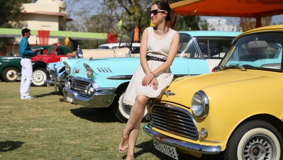A visitor poses for a photograph  in front of a vintage car at the 19th Vintage & Classic Car Rally in Jaipur. The three day exhibition and rally consists  of around 100 vintage and classic cars from over the country. (Himanshu Vyas\ HT Photo)