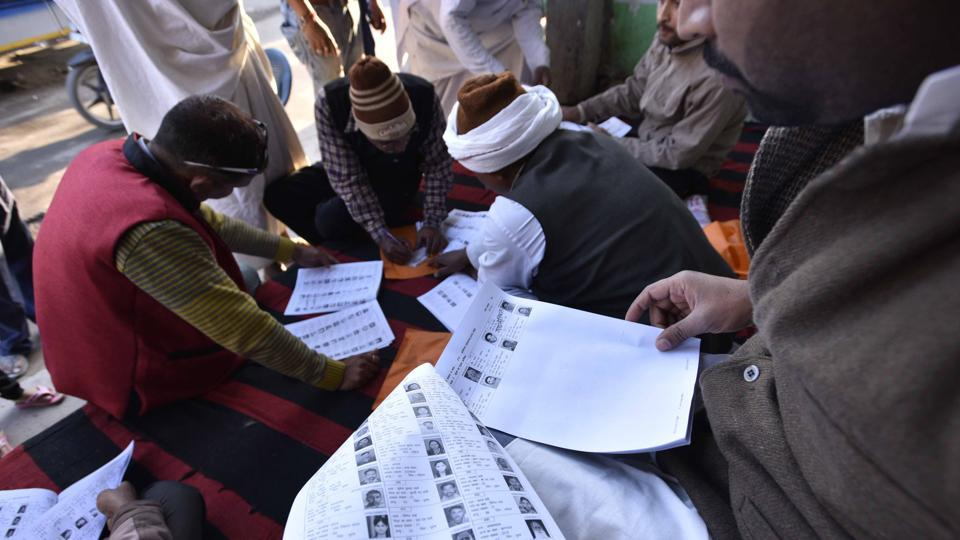 Poring over voter lists at a polling station at Ayodhya. An estimated 12 to 13% of voters turned out to exercise their franchise till 10am across these districts. (Arun Sharma/HT PHOTO)
