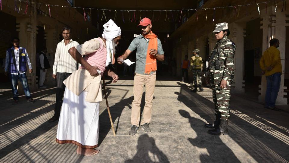 People cast their votes as a policewoman stands guard at a polling station.  Ayodhya is an important constituency for the BJP as it rose to power on the back of the Ram Mandir movement and won the assembly seat four times before suffering a shock defeat to the SP in 2012. (Arun Sharma/HT PHOTO)