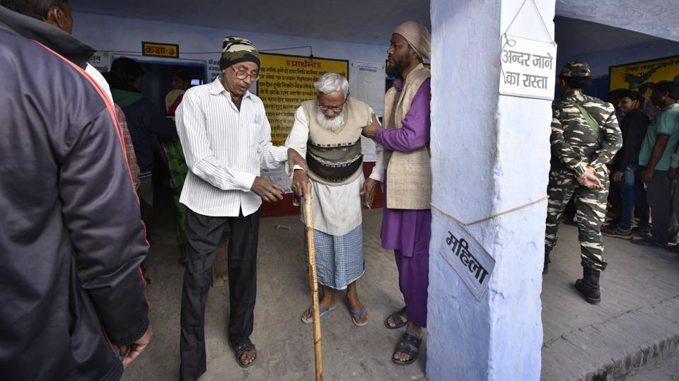 An old man is helped as he emerges after casting his vote today. (Arun Sharma/HT PHOTO)