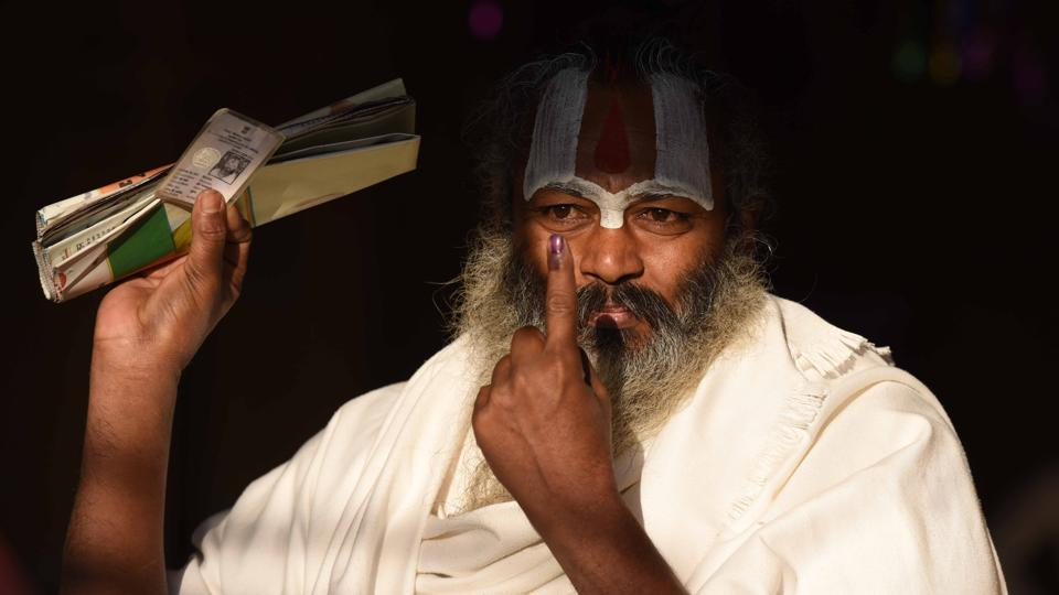 A sadhu shows his inked finger after casting his vote at a polling booth during the fifth phase of UP assembly election in Ayodhya on Monday.