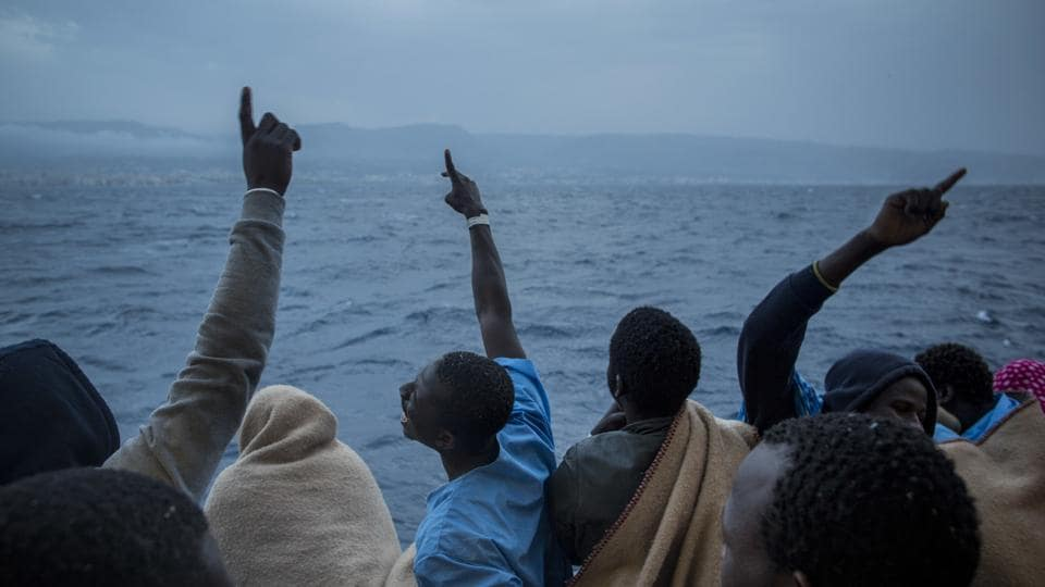 African refugees and migrants celebrate their arrival in Italy . (Santi Palacios / AP)