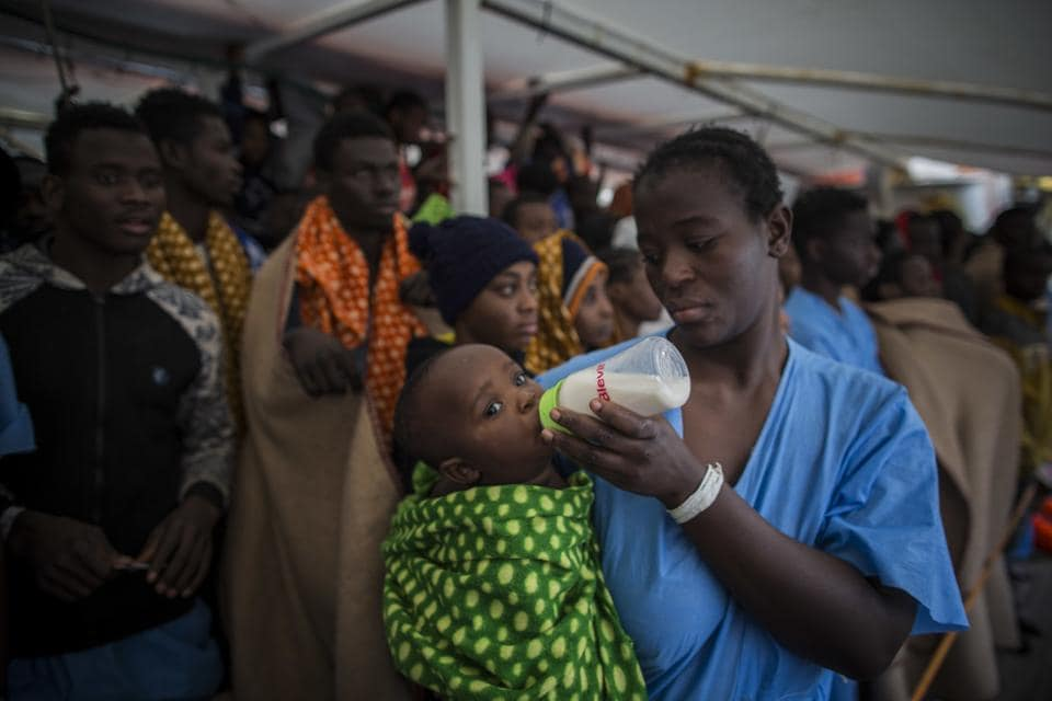 A woman from Ivory Coast feeds her baby aboard the Golfo Azurro, the Spanish NGO Proactiva Open Arms rescue ship, as she waits with other refugees and migrants, to disembark at the Italian port of Reggio Calabria. (Santi Palacios / AP)