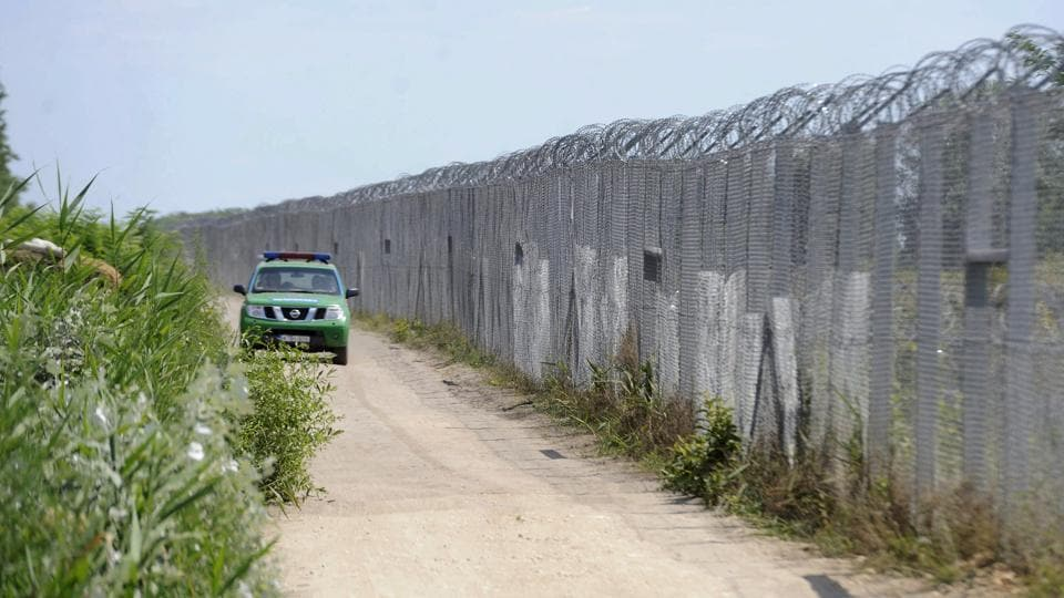 A Hungarian police vehicle patrols by the border fence between Hungary and Serbia near Asotthalom, Hungary.