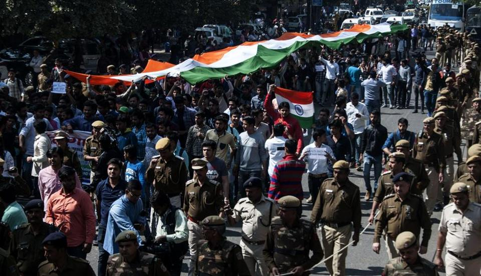 Students of the Akhil Bharatiya Vidyarthi Parishad (ABVP) are watched by security personnel as they shout slogans while carrying a giant Indian tricolour during a 'Tiranga March' on the campus of Delhi University in New Delhi on Monday.